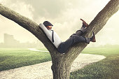 Lazy business man enjoying break on a tree