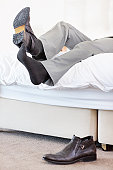 Lazy man removing his shoes on the bed