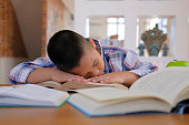 lazy stressed young little asian kid boy  resting sleeping on desk. child fall asleep. children tired from studying in classroom. childhood education
