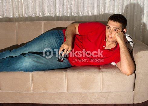 Lazy Young Man Watching Tv On Comfortable Sofa Stock Photo | Thinkstock