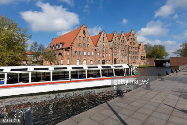 Lübeck: Historic salt store buildings with sightseeing boat on the Obertrave River (Schleswig-Holstein/ Germany)
