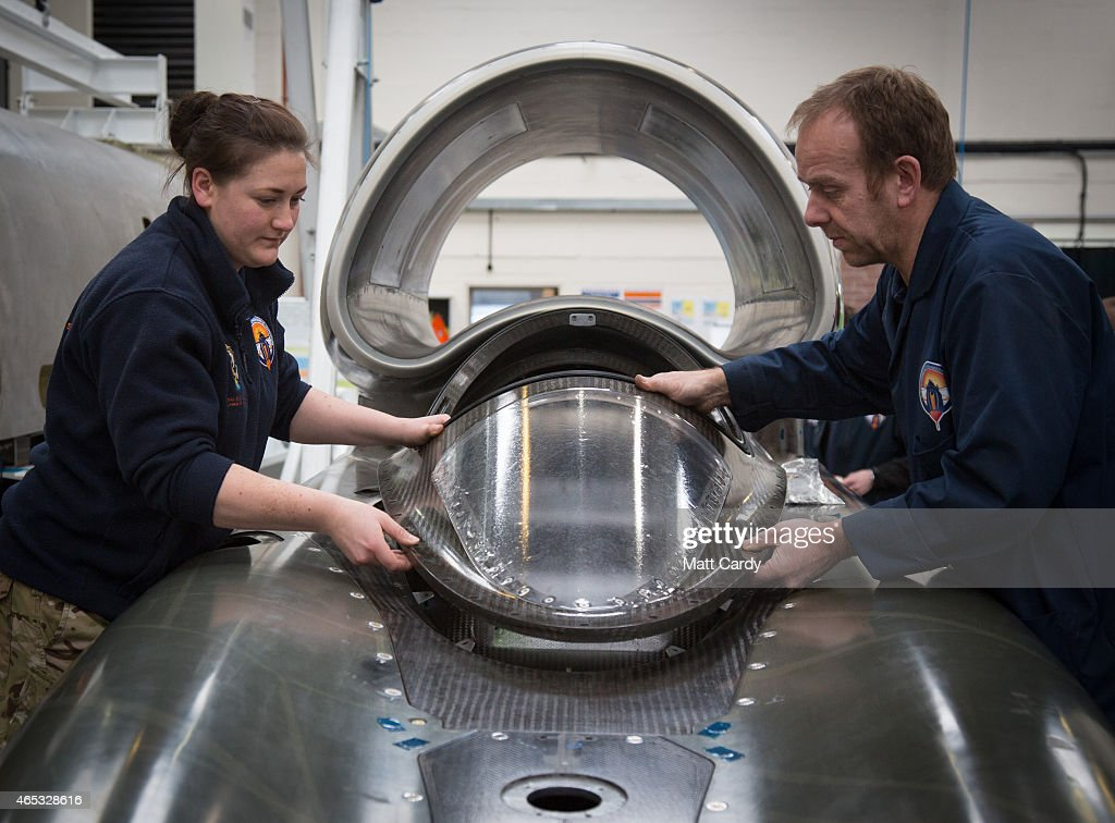 Cpl Kayleigh Williams from the Royal Electrical and Mechanical Engineers and build technician Rupert ByrceMorris put the cockpit glass cover in place...