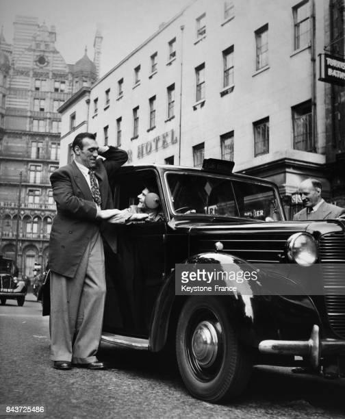 Le boxeur italien Primo Carnera en conversation avec un chauffeur de taxi à la vitre de la voiture circa 1930 à Londres RoyaumeUni