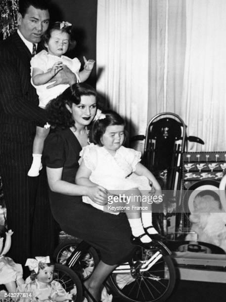Le boxeur Jack Dempsey avec sa femme l'actrice Hannah Williams et ses deux filles Joan et Barbara à leur domicile pour Noël circa 1940 aux EtatsUnis