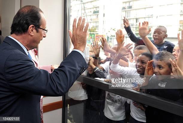 Le candidat à la primaire PS François Hollande salue par des élèves alors qu'il visite une école lors d'un déplacement sur le thème de l'éducation à...