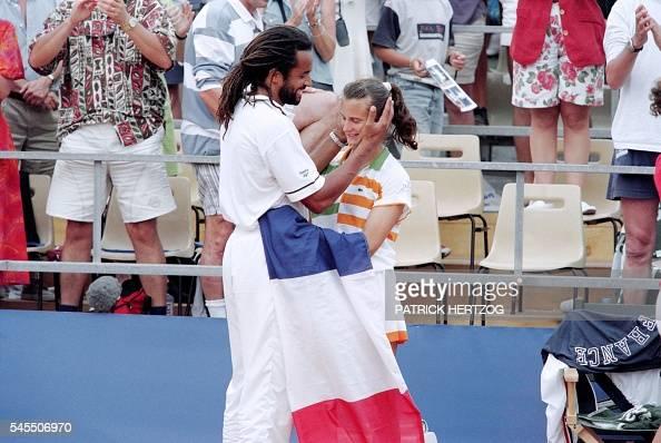 le capitaine de l'équipe de France féminine de tennis Yannick Noah félicite la joueuse Alexandra Fusai le 13 juillet 1997 à Nice à l'issue du dernier...