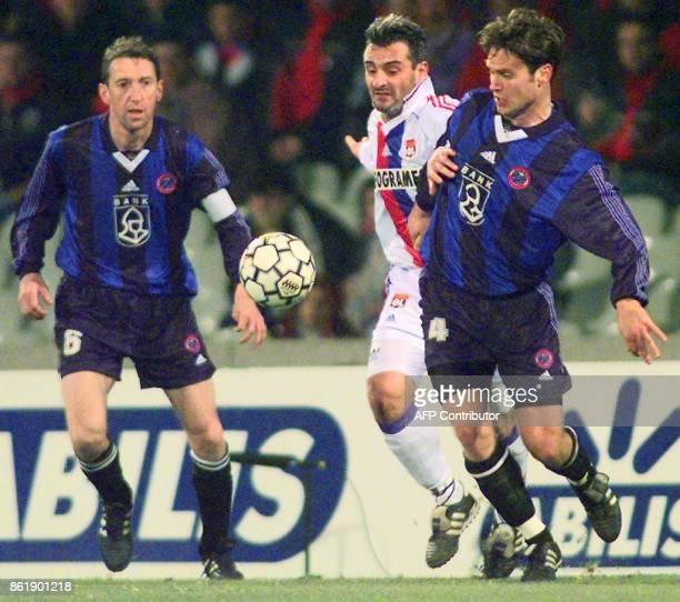 le capitaine lyonnais Alain Caveglia tente de s'infiltrer entre le capitaine de l'équipe belge Franky Van Der Elst et Milan Lesnjac le 24 novembre au...