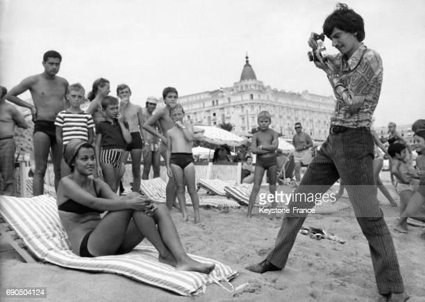 Le chanteur Antoine photographie une jeune femme en bikini sur la plage du Grand Hôtel le 24 août 1967 à Cannes France