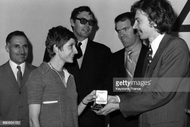 Le chanteur Antoine remet un Coq d'Or à Nicole Duclos en présence de Mimoun Ignace Heinrich et Bill Toomey au club du Coq Sportif pour récompenser...