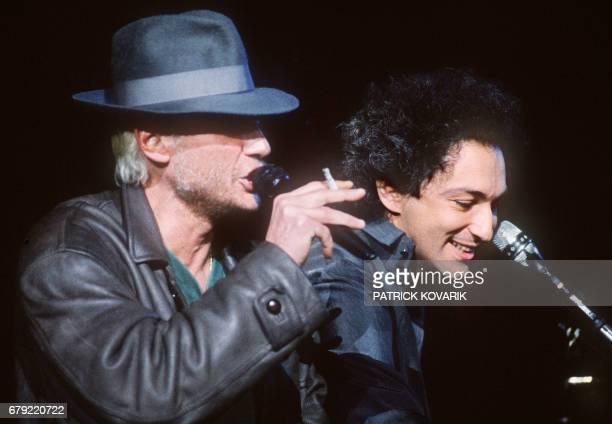 Le chanteur de rock et acteur français Johnny Hallyday chante accompagné au piano par Michel Berger le 11 avril 1986 sur la scène du Zénith à Paris...