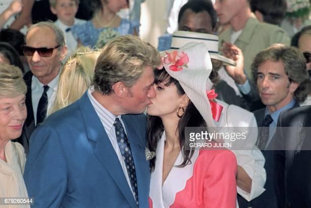 Le chanteur de rock et acteur français Johnny Hallyday embrasse le 09 juillet 1990 à Ramatuelle son épouse Adeline Blondieau après leur mariage à la...