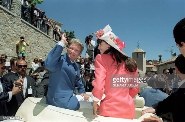 Le chanteur de rock et acteur français Johnny Hallyday salue la foule le 09 juillet 1990 à Ramatuelle en compagnie de son épouse Adeline Blondieau...