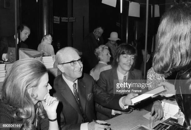 Le chanteur Maurice Chevalier dédicace un livre à une visiteuse à la XIème vente de livres des écrivainscombattants à la Maison de la Chimie en...