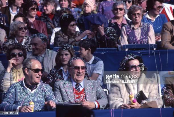 Le chanteur Tino Rossi et son épouse assistent à un défilé du Carnaval avec à gauche l'académicien Alain Decaux en février 1983 à Nice France