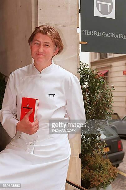 le chef Pierre Gagnaire pose le 03 mars le guide Michelin à la main devant l'entrée de son restaurant parisien qui vient d'obtenir deux étoiles dans...