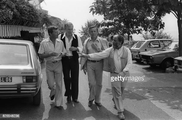 Le comédien et animateur de radio José Artur l'acteur Yves Montand le peintre Lignon et le sculpteur César discutent dans les rues de...