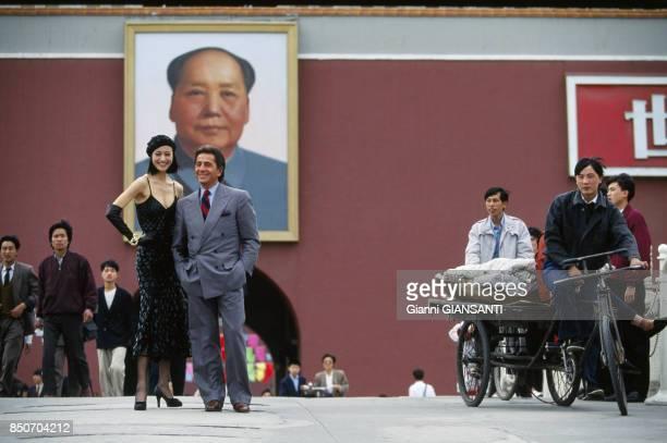 Le couturier italien Valentino Garavani pose avec un mannequin devant un portrait de Mao à Pékin en mai 1993 Chine