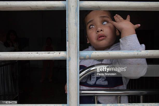 Le Dang Kietage 5 is blind and can't speak looks out from a window at the Duc Son Pagoda March 9 in Hue Vietnam There are 15 handicapped children...