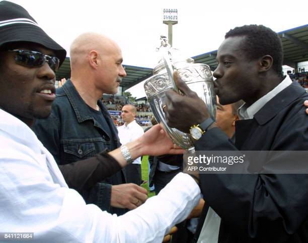 le défenseur central sénégalais de Lorient Malik Diop embrasse le trophée aux côtés de son coéquipier l'attaquant Pascal Feindouno et de l'entraîneur...