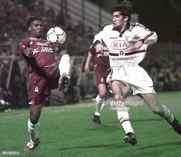 le défenseur messin Rigobert Song tente de contrôler le ballon devant l'attaquant lensois Anton Drobnjak le 29 mars au stade SaintSymphorien à Metz...