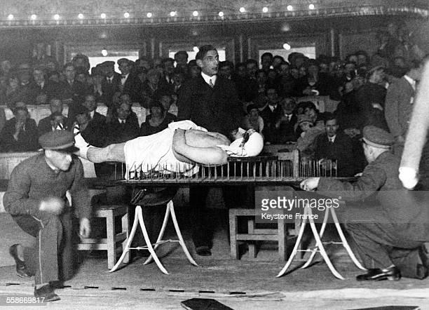 Le fakir Tahra Bey allongé sur une planche à clous lors d'un numéro dans un cirque à Paris France