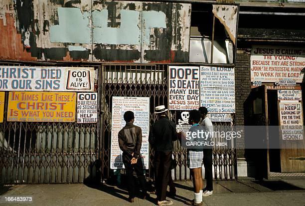 The Ghetto New York City Harlem juillet 1970 le ghetto trois enfants lisent les affiches de propagande pentecôtiste placardées sur un rezdechaussée...