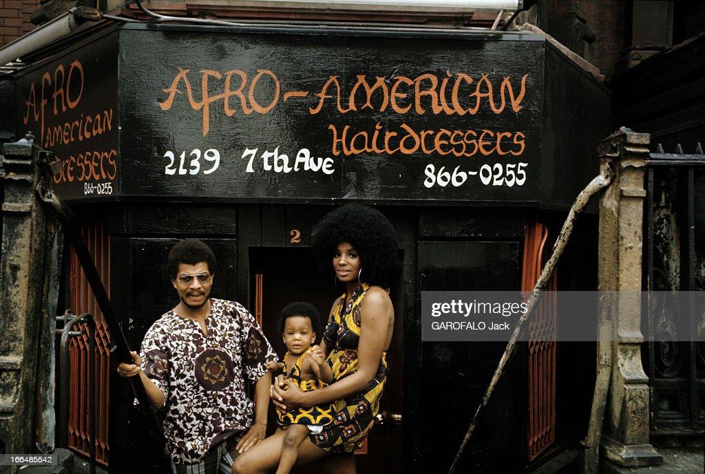 The Ghetto. New York City- Harlem- juillet 1970: le ghetto; une jeune femme afro-américaine, portant une perruque 'dernier cri' porte son enfant coiffé d'une permanente, devant le salon de coiffure, son propriétaire à ses côtés.