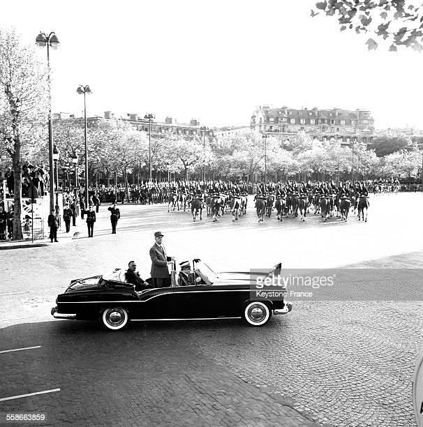 Le Général de Gaulle debout dans la voiture répond aux acclamations de la foule à ses côtés le Premier ministre Georges Pompidou à Paris France le 8...