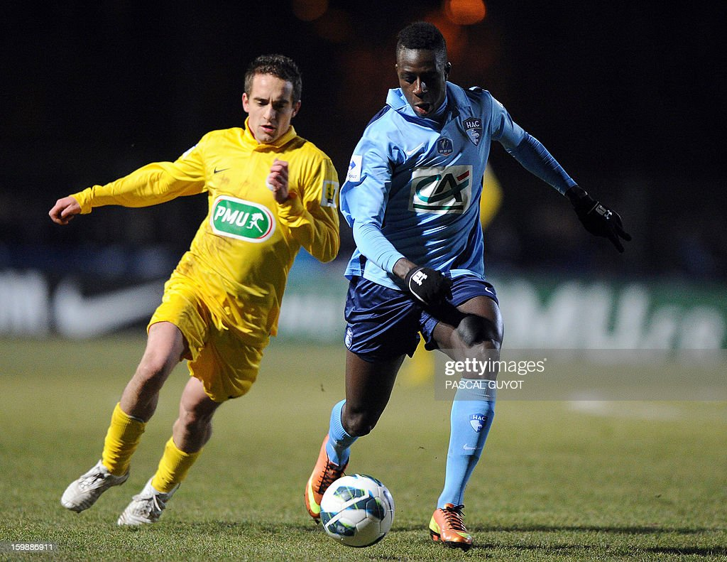 Le Havre's Benjamin Mendy (R) with Mende's Nicolas Brunel (L) during the French Cup football match Mende vs Le Havre at the Jean-Jacques Delmas stadium on January 22, 2013, in Mende.