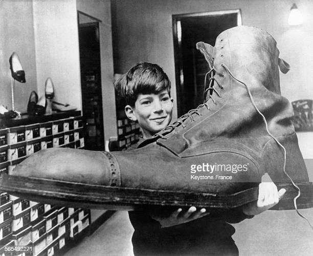 Le jeune Gordon porte la chaussure géante qui est habituellement présentée dans la vitrine du magasin de son père et qu'il nettoie toutes les...