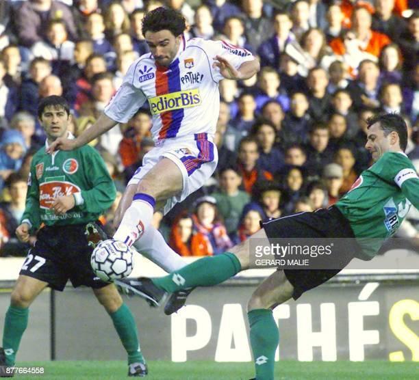 le joueur de Lyon Patrice Carteron effectue un tir malgré l'opposition des Sédanais Luis Satorra et Djoni Novak le 26 mars 2000 au stade de Gerland à...