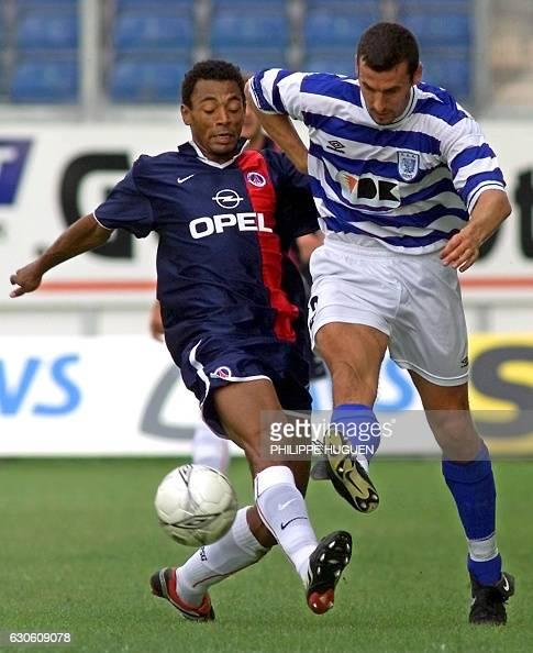 le joueur parisien Edouard Cissé est à la lutte avec le joueur de Gand Jacky Peetersl le 25 juillet 2001 au stade Jules Otten de Gand lors du match...