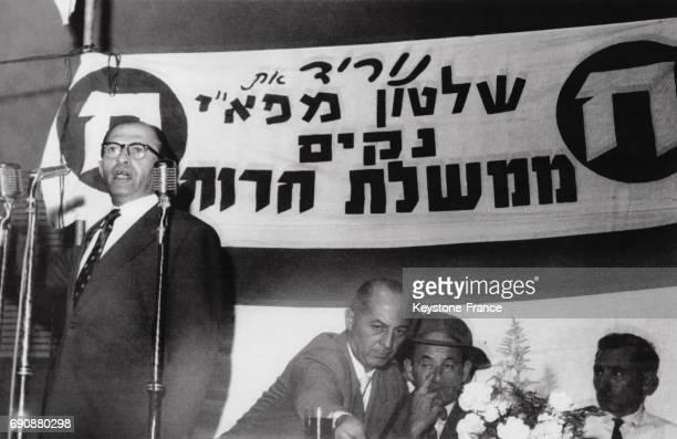 Le leader de l'opposition et chef du parti Heirut Menahem Begin prononçant un discours lors d'un meeting politique derrière lui est inscrit sur la...