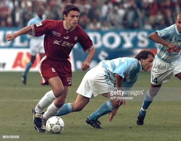 le Lorrain Vladan Luvik est aux prises avec les Strasbourgeois Stephane Raschke et Karim N'Gnoghi le 05 septembre au stade de la Meinau lors de la...