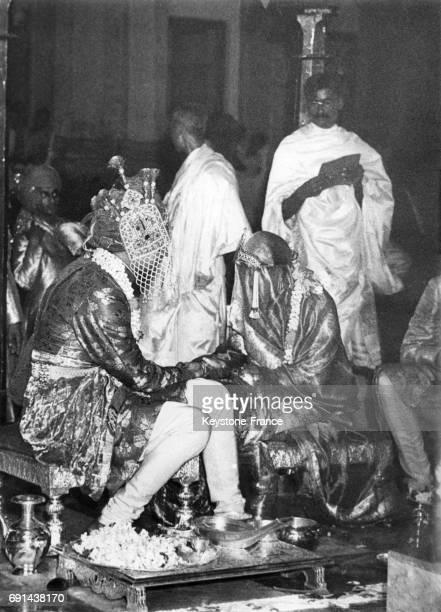 Le maharajah et la princesse se tiennent la main durant la cérémonie la mariée parée de coûteux bijoux et le marié est voilé en Inde le 25 mai 1940