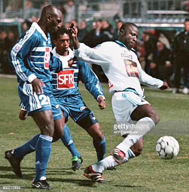 le Marseillais Ibrahim Bakayoko passe les Bastiais Zoumana Camara et Morlaye Souhma le 09 janvier 2000 au stade ArmandCésari à Furiani lors de la...