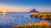 Panoramic view of famous Le Mont Saint Michel tidal island in beautiful golden evening light at sunset in summer, Normandy, France.