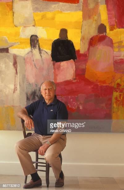 Le peintre Bernard Cathelin assis devant une de ses oeuvres en octobre 1993 en France