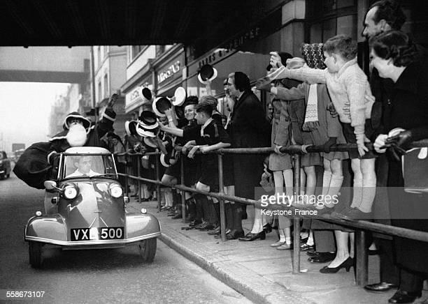 Le Père Noël arrive au magasin 'Bon Marché' dans sa Messerschmitt Cabon Scooter acclamé par la foule le 15 novembre 1958 à Brixton RoyaumeUni