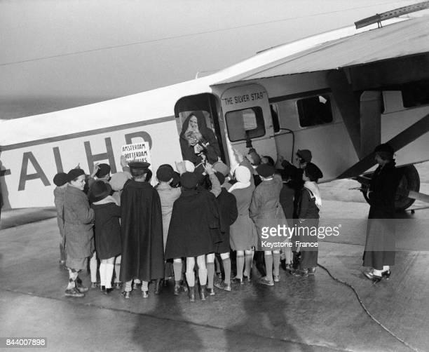 Le père Noël distribuant des cadeaux à un groupe d'enfants d'une école de la région parisienne à son arrivée au Bourget France le 19 décembre 1932