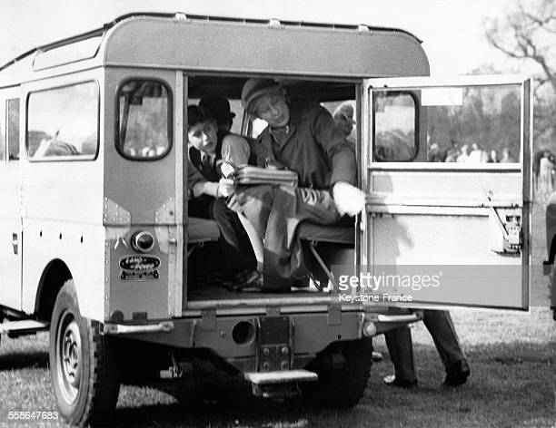 Le Prince Charles assis a cote de la Princesse Margaret se penche pour regarder quelque chose hors de la voiture apres avoir visite l'arene de...