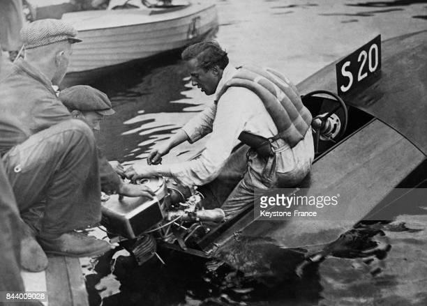 Le prince Charles de Suède procède à un réglage du moteur de son horsbord avant de participer à une course en Suède le 23 juillet 1935