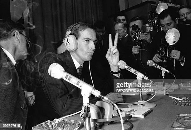 Le professeur Christiaan Barnard chirurgien cardiaque fait le V de la victoire devant les micros de RTL et les photographes circa 1960