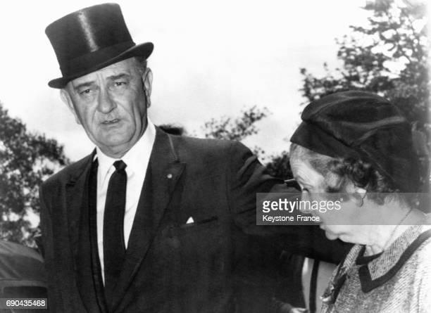 Le président américain Lyndon B Johnson accompagné de l'épouse de l'ambassadeur américain après la messe du souvenir en l'honneur du premier minsitre...