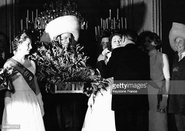 Le président de la république française René Coty embrasse la Reine des Halles à côté d'un Fort des Halles qui tient une grande corbeille de muguet...