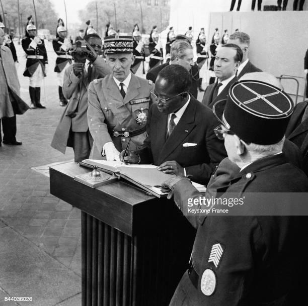 Le président sénégalais Léopold Sédar Senghor signe le Livre d'or sous l'Arc de Triomphe derrière lui le Premier ministre Michel Debré à Paris France...