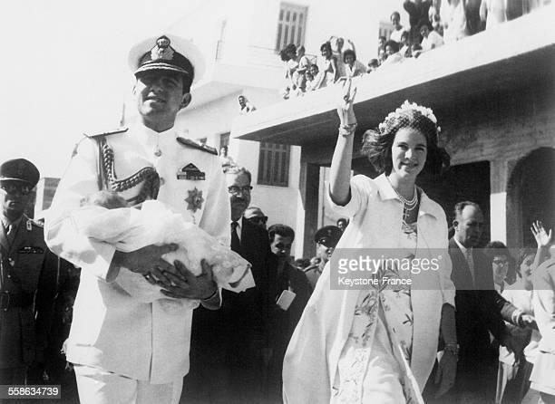 Le roi Constantin de Grèce tenant dans ses bras sa fille la reine AnneMarie à ses côtés lors d'une escale sur une île grecque pour présenter la...