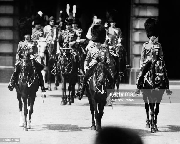 Le roi d'Angleterre au centre à sa gauche le duc d'York et à sa droite le prince de Galles quitte le Palais de Buckingham à cheval pour se rendre à...