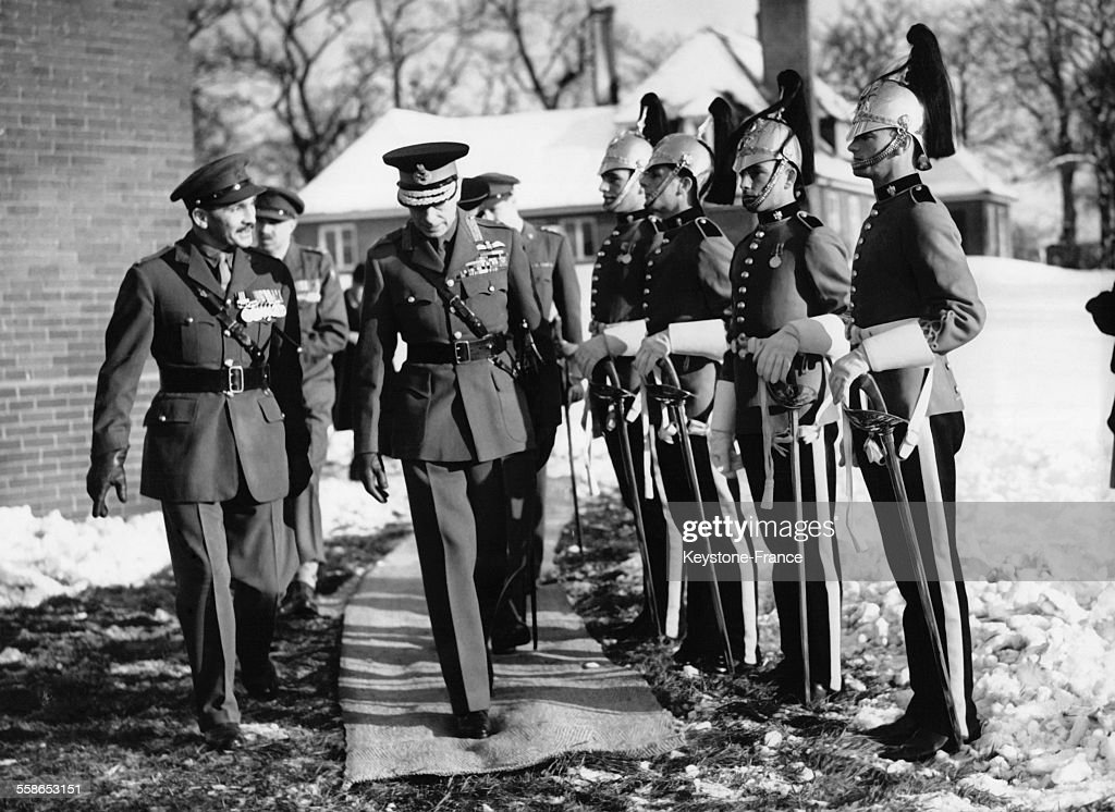 Le roi George VI visite les Royal Dragoons quatre soldats au garde a vous et un officier bien emmitoufle sourit le 6 decembre 1950 a Chester...