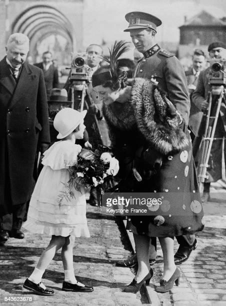 Le roi Léopold III et la reine Astrid recevant des fleurs des mains d'une petite fille à l'occasion de l'inauguration d'un canal à Anvers Belgique le...